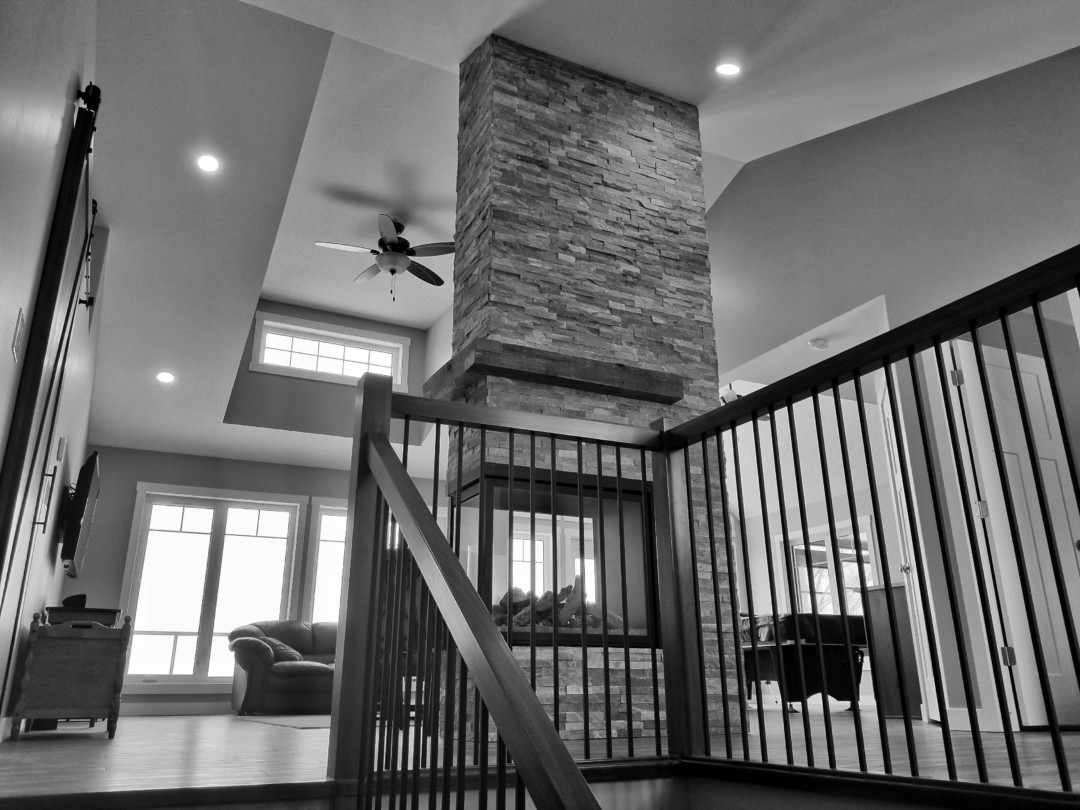Custom Two Storey Lakehouse built with vaulted ceilings, and 4 sided stacked stone fireplace